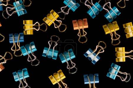 Photo pour Vue de dessus de trombones colorés, petits, éparpillés jaune, orange et bleu isolés sur noir - image libre de droit