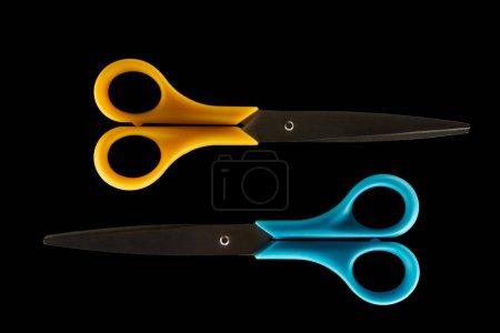 Photo pour Vue de dessus deux ciseaux fermés isolés sur noir - image libre de droit