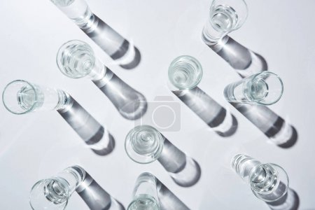 Photo for Top view of transparent glasses with water on white background with shadows - Royalty Free Image