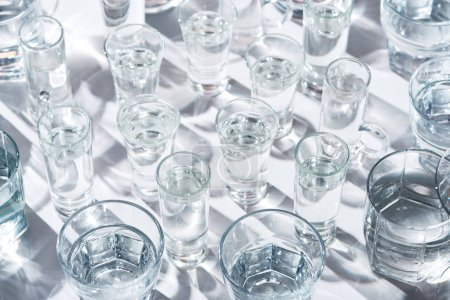 close up view of transparent glasses with water on white background