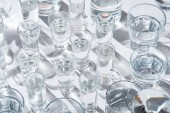 """Постер, картина, фотообои """"close up view of transparent glasses with water on white background with shadows"""""""