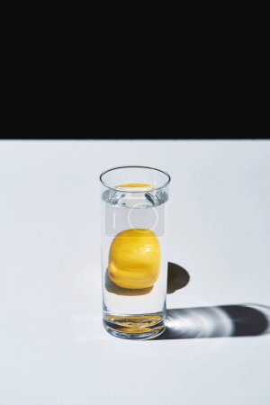 Photo for Transparent glass with water and whole lemon on white surface isolated on black - Royalty Free Image