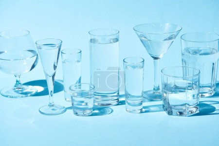transparent glasses with clear water on blue background