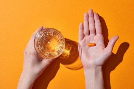 Photo pour Vue recadrée de la femme tenant la pilule sur la paume près du verre avec de l'eau sur fond orange - image libre de droit