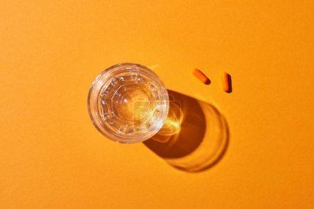 Photo pour Vue supérieure des pillules près du verre avec l'eau sur le fond orange - image libre de droit
