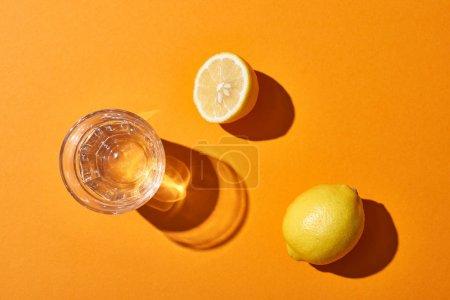 Photo pour Vue supérieure du verre avec l'eau près des citrons jaunes sur le fond orange - image libre de droit