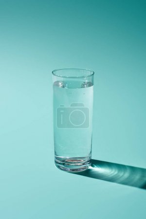 transparent glass with water on turquoise background