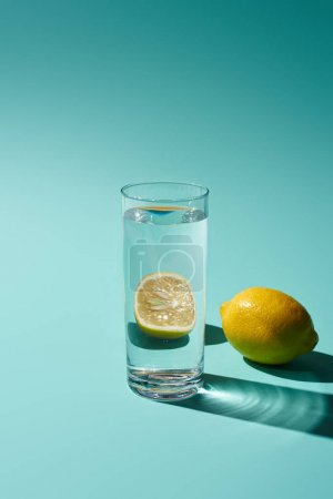 Photo for Transparent glass with  water and lemon on turquoise background - Royalty Free Image