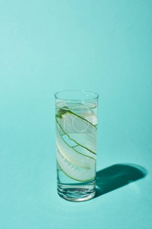 Photo pour Transparent glass with pure water and cucumber slices on turquoise background - image libre de droit