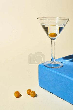 Photo for Transparent glass with cocktail on blue cube on beige background - Royalty Free Image