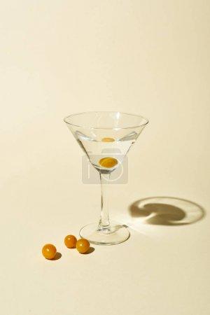 Foto de Transparent glass with cocktail and berries on beige background - Imagen libre de derechos