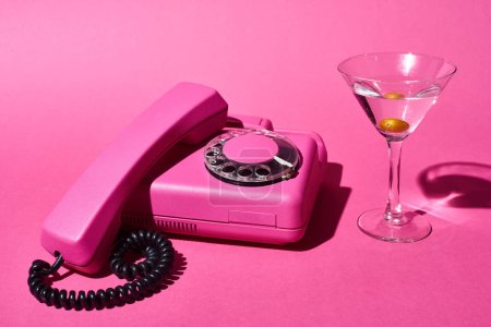 Photo for Cocktail with olive and retro bright pink telephone on pink background - Royalty Free Image
