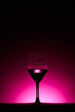 Foto de Cristal transparente con cóctel sobre fondo rosa con luz trasera - Imagen libre de derechos