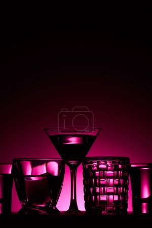 Photo for Transparent glasses with liquid on dark background with pink illumination - Royalty Free Image