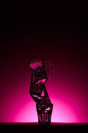 Foto de Transparent glasses on dark background with pink illumination - Imagen libre de derechos