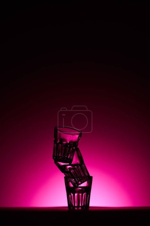 Photo pour Pyramid of glasses on dark background with pink illumination - image libre de droit