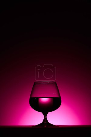 Photo for Transparent glass with liquid on dark background with pink illumination - Royalty Free Image