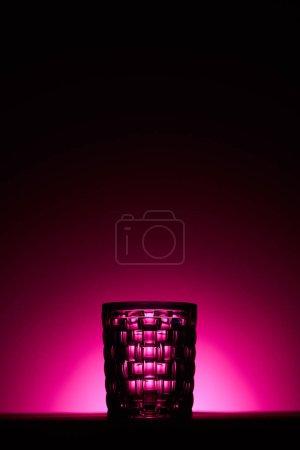Foto de Transparent textured glass on dark background with pink illumination - Imagen libre de derechos
