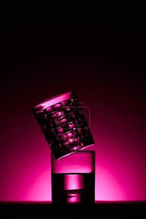Photo pour Transparent glasses with water on dark background with pink illumination - image libre de droit