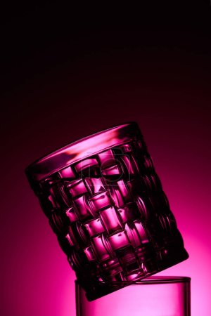 Photo pour Close up view of transparent textured glass on dark background with pink illumination - image libre de droit