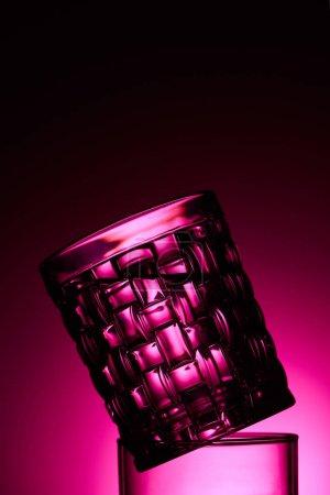 Foto de Close up view of transparent textured glass on dark background with pink illumination - Imagen libre de derechos