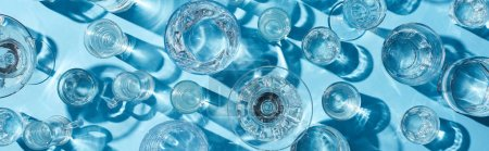 Photo for Top view of glasses with clear water and shadows on blue surface, panoramic shot - Royalty Free Image