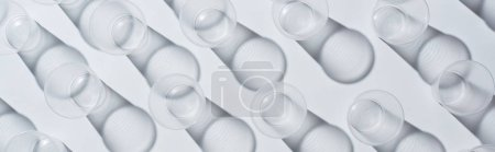 top view of disposable empty cups on white background with shadows, panoramic shot