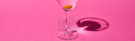 Photo for Panoramic shot of transparent glass with cocktail and olive on pink background - Royalty Free Image