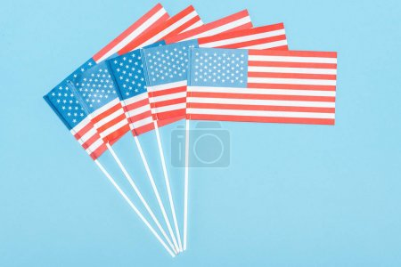 vista superior de banderas americanas sobre palos sobre fondo azul