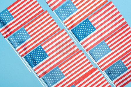 Photo pour Couché plat avec des drapeaux américains sur des bâtons sur fond bleu - image libre de droit