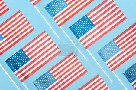 Photo pour Plat gisait avec des drapeaux américains nationaux sur des bâtons sur le fond bleu - image libre de droit