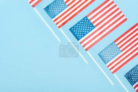 Photo pour Couché plat avec des drapeaux américains sur des bâtons sur fond bleu avec espace de copie - image libre de droit