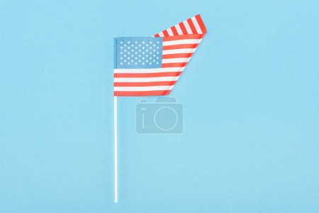 Photo for Top view of american flag on stick on blue background - Royalty Free Image