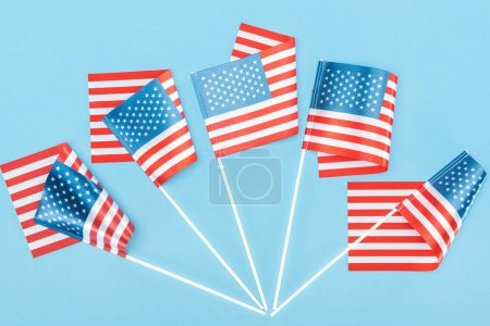 Photo pour Vue de dessus des drapeaux américains traditionnels sur bâtons sur fond bleu - image libre de droit