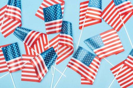 vista superior de banderas americanas sobre palos dispersos sobre fondo azul