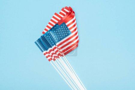 Foto de Vista superior de banderas americanas sobre palos apilados sobre fondo azul - Imagen libre de derechos