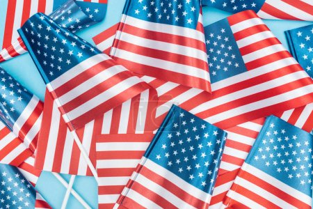 Photo for Top view of national american flags on sticks scattered on blue background - Royalty Free Image