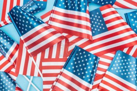 Photo pour Vue supérieure des drapeaux américains nationaux sur des bâtons dispersés sur le fond bleu - image libre de droit
