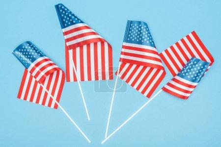Foto de Vista superior de banderas americanas satinadas en palos sobre fondo azul - Imagen libre de derechos