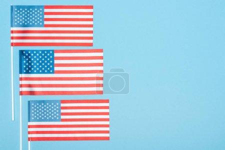 Photo pour Vue supérieure des drapeaux d'usa sur des bâtons sur le fond bleu - image libre de droit