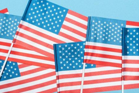 Photo pour Fermer vers le haut la vue des drapeaux américains décoratifs sur des bâtons sur le fond bleu - image libre de droit