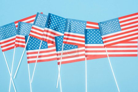 top view of national usa flags on sticks on blue background