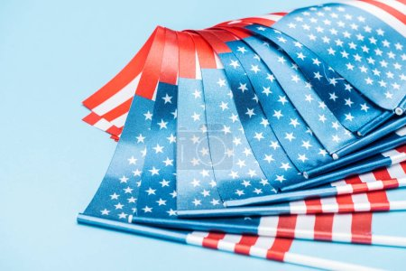 Photo for Close up view of satin american flags on blue background - Royalty Free Image
