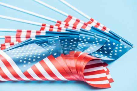 Photo pour Vue rapprochée des drapeaux américains sur bâtons sur fond bleu - image libre de droit