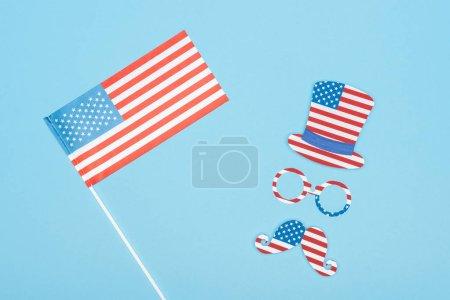 Photo pour Vue du dessus du drapeau des Etats-Unis sur bâton près de moustache de papier coupé, chapeau et lunettes sur fond bleu - image libre de droit