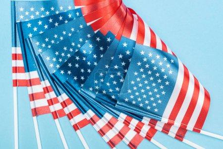 Photo pour Vue rapprochée des drapeaux américains en soie sur bâtons sur fond bleu - image libre de droit