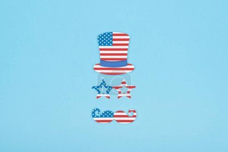 flat lay with paper cut mustache, glasses and hat made of usa flags on blue background