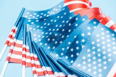 Photo pour Vue rapprochée de la soie nationale Etats-Unis drapeaux sur bâtons sur fond bleu - image libre de droit