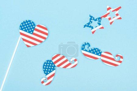 Photo pour Vue du dessus des verres décoratifs, moustache et coeur en drapeaux américains sur fond bleu - image libre de droit
