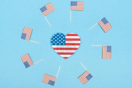 marco redondo de papel cortado banderas americanas decorativas en palos de madera y corazón hecho de estrellas y rayas sobre fondo azul